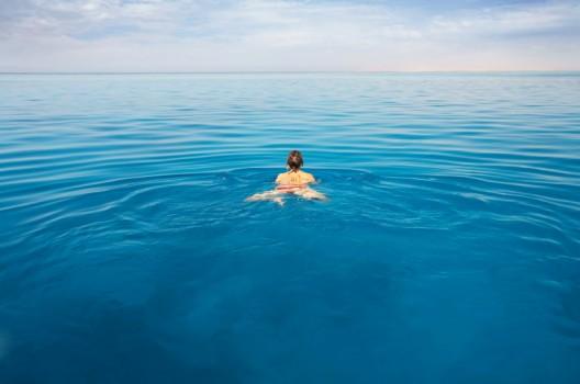 Una joven nada en el mar abierto